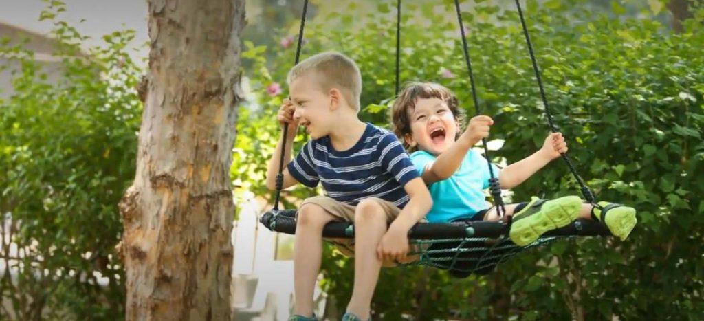 Des enfants qui s'amuse sur une balançoire nid d'oiseau accrochée à un arbre